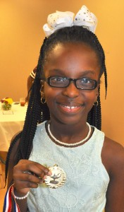 Jaliyah Jackson shows of a Character In Action medal she received at the annual CIA Banquet held Thursday, Sept. 27 at the Hayneville Senior Center. Signal photo/Fred Guarino.